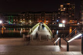 Illuminated foot bridge in over North Dock in Canary Wharf by night — Stock Photo