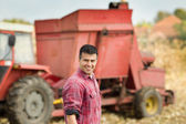 Farmer with agricultural machinery in field — Stock Photo