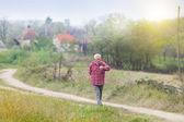 Senior man walkng in village — Stock Photo