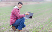Man with laptop in the field — Stock Photo