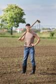 Farmer with hoe in corn field — Stock Photo