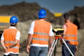 Theodolite and workers at construction site — Stock Photo