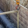 Crane hook hold up pipe in trench — Stock Photo #53471595