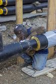Welder welding underground steel pipe kneels on ground 2 — Foto de Stock