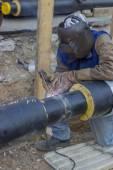 Welder welding underground steel pipe kneels on ground 3 — Foto de Stock