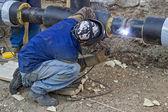 Welder welding underground steel pipe kneels on ground — Foto de Stock
