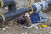 Welder welding underground steel pipe lying on ground 3 — Foto de Stock