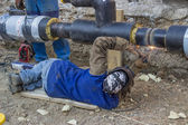 Welder welding underground steel pipe lying on ground — Stock Photo