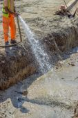 Worker wets the crushed aggregate base course surface — ストック写真