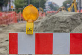 Construction barrier sign with yellow warning light — Stock Photo