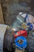 Welder welding heat pipes in trench — Stock Photo