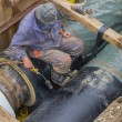 Insulation worker applied tar coating on underground heating pip — Stock Photo #54111269