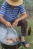 Äldre man med en stråhatt på en grill — Stockfoto