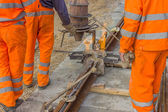 Workers in orange welding tracks — Stock Photo