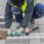 Construction worker installing sidewalk pavement — Stock Photo #61611847