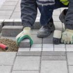 Construction worker setting sidewalk pavement — Stock Photo #61612099