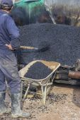Asphalt workers with a shovel filling wheelbarrow with asphalt — Stock Photo