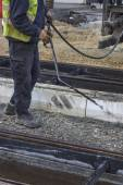 Road worker spraying manually bitumen emulsion 2 — Stock Photo