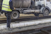 Road worker spraying manually bitumen emulsion — Stock Photo
