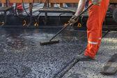 Crew placing mastic asphalt road — Stock Photo