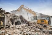 Excavator demolishing barracks — Stock Photo