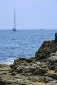 Rocks and sailboat — Stock Photo
