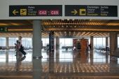 Airport interior with information signs and people reflected in shiny floor surface — Stock Photo