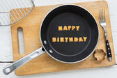 Letter biscuits word HAPPY BIRTHDAY and cooking equipments. — Stock Photo