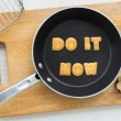 Alphabet crackers quote DO IT NOW putting in pan — Stock Photo #76574803