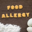 Letter biscuits word FOOD ALLERGY on kitchen table background — Stock Photo #76578027
