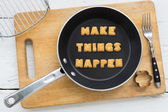 Letter cookies quote MAKE THINGS HAPPEN and kitchen utensils — Stock Photo