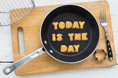 Cookie biscuits quote TODAY IS THE DAY in frying pan — Stock Photo