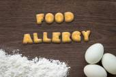 Letter biscuits word FOOD ALLERGY on kitchen table background — Stock Photo