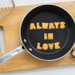Cookie biscuits quote ALWAYS IN LOVE in frying pan — Stock Photo #76976271