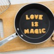 Cookie biscuits quote LOVE IS MAGIC in frying pan — Stock Photo #77376836