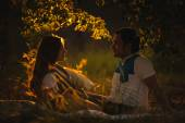 Mutlu gülümseyen çift rahatlatıcı akşam yeşil çimenlerin üzerinde — Stok fotoğraf