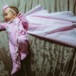 Image of cute little girl in pink suit and cloak indoor — Stock Photo #55111399
