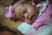 Image of cute little girl in pink suit indoor. Newborn baby — Stock Photo