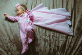 Image of cute little girl in pink suit and cloak indoor — Stock Photo