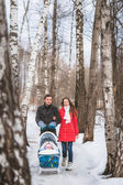 Young family walk in winter wood. Parent pulling sledge — Stock Photo