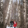 Young family walk in winter wood. Parent pulling sledge — Stock Photo #68881537