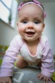 Adorable baby girl crawls on all fours floor at home — Stockfoto