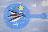 Fresh anchovy fish on blue wooden kitchen board. — Stock Photo