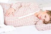 Young pregnant woman luxuriates in a white bed. — Stock Photo