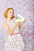 Parlak bir arka plan üzerine bir hediye ile kızıl saçlı genç kız. güzel bir kız portresi. — Stok fotoğraf
