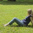 Beautiful pregnant blonde lying on green grass. Portrait of pregnant woman. Outdoors — Stock Photo #54756385