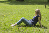 Beautiful pregnant blonde lying on green grass. Portrait of pregnant woman. Outdoors — Stock Photo