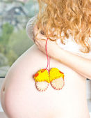 Beautiful pregnant blonde standing near the window and enjoy the sun. — Stock Photo