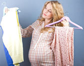 Beautiful pregnant blonde chooses clothes. Portrait of pregnant woman. fashion portrait.woman couple shopping portrait. — Stock Photo
