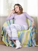 Beautiful pregnant blonde listens to classical music on headphones. Portrait of pregnant woman. The development of the child in the womb — Stockfoto